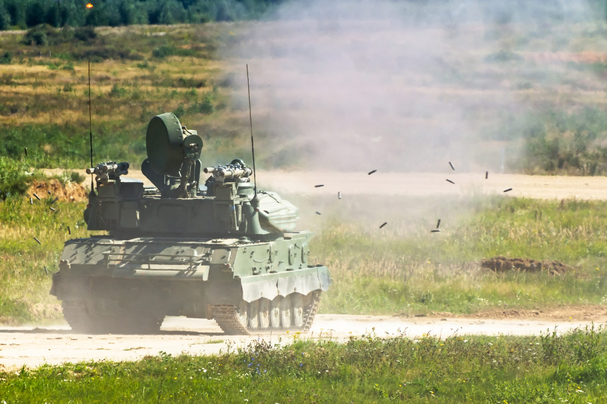Shooting armored personnel carrier on the field during military operations. The falling lysis from the cartridges is seen.