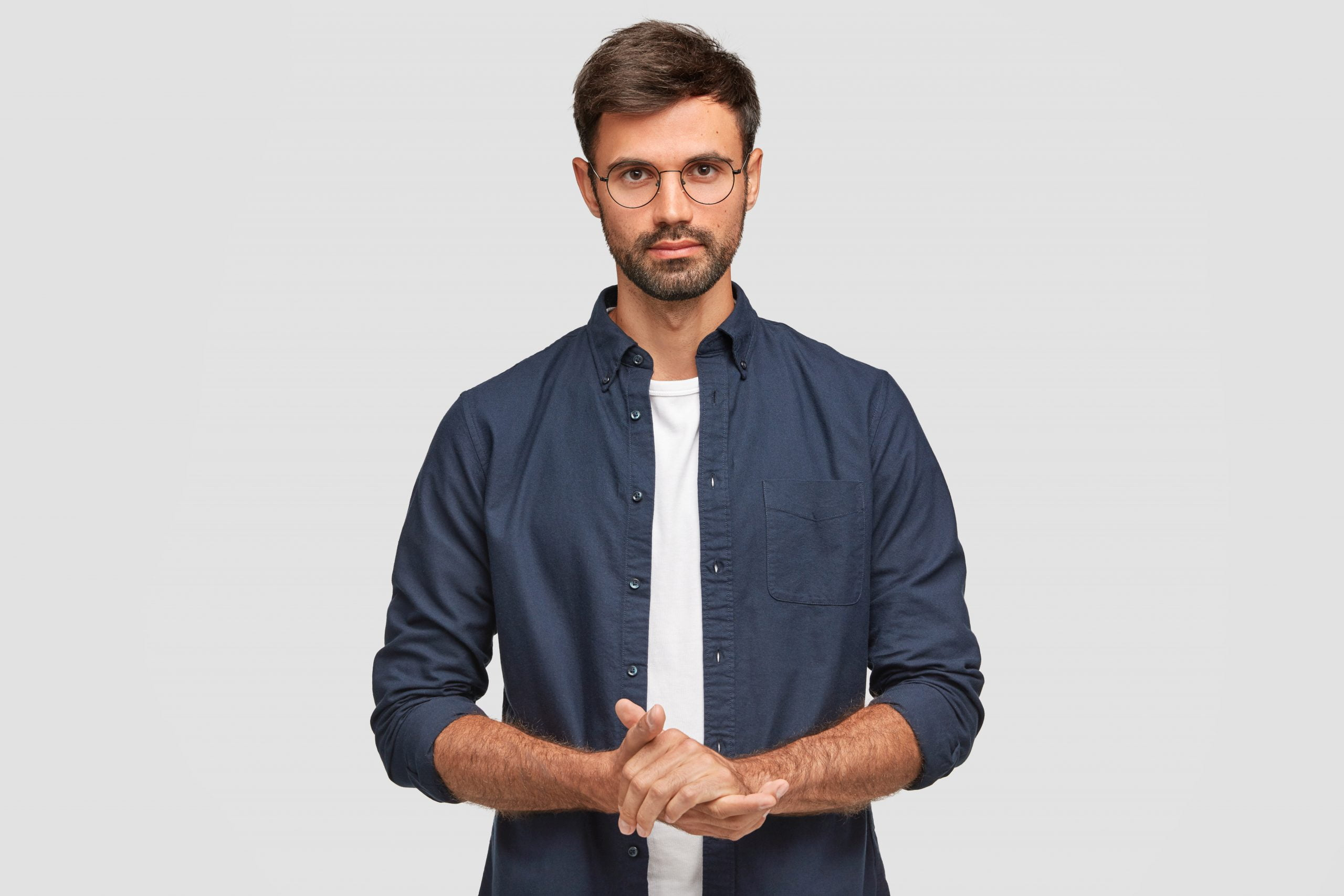waist up portrait handsome serious unshaven male keeps hands together dressed dark blue shirt has talk with interlocutor stands against white wall self confident man freelancer 1 scaled